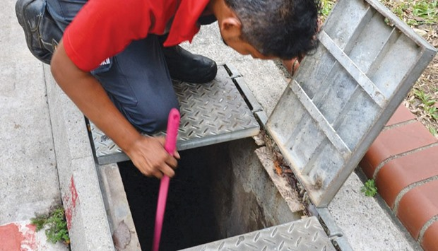 A pest control worker checks for mosquitoes breeding in the drain at Bedok North housing estate in S