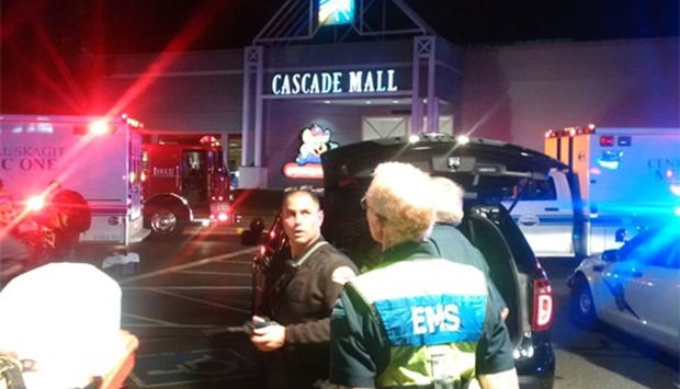 Medics wait to gain access to the Cascade Mall after shooting
