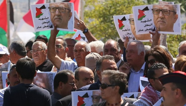 Protesters shout slogans and hold portraits of Jordanian writer Nahed Hattar, who was shot dead