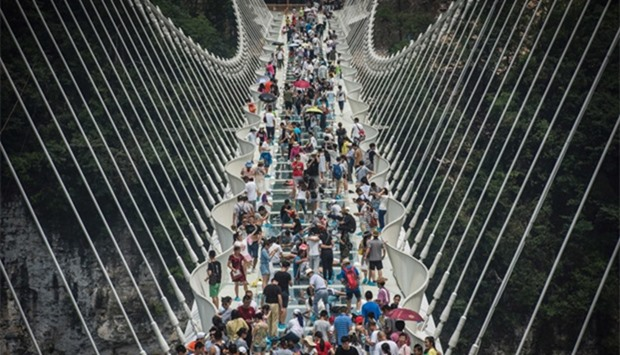 visitors crossing the world's highest and longest glass-bottomed bridge