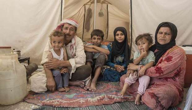 A Syrian family  sitting inside a tent in which they live, in a camp for people displaced by the war