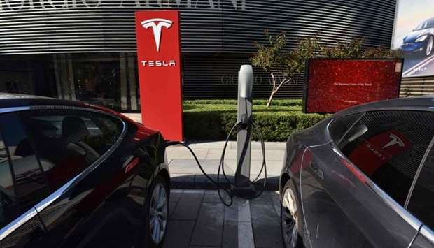 Tesla cars charge at a Tesla charging station outside a shopping mall in Beijing