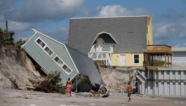 Local residents look at a collapsed coastal house after Hurricane Irma passed the area in Vilano Bea
