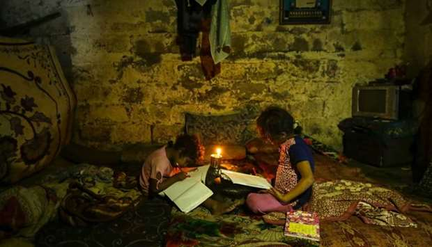 Palestinian children do their homeworks during a power cut in an impoverished area in Gaza City.