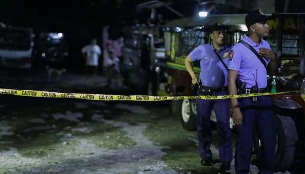 Policemen stand behind a police line in Manila