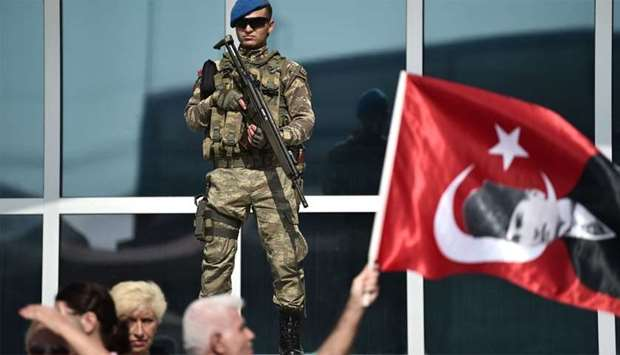 A Turkish gendarme stands guard while a protester waves a flag with an image of Mustafa Kemal Atatur