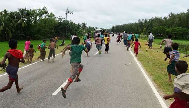 Rohingya Muslim refugees children follow a vehicle with relief supplies