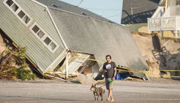 Jose Orosz walks his dog by a beachfront home destroyed by Irma.