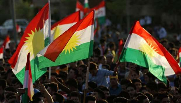 Iraqi Kurds gather in the street flying Kurdish flags as they urge people to vote in the upcoming in
