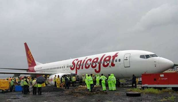 Aircraft recovery team members and airport officials inspect the spiceJet plane that overshot the Mu