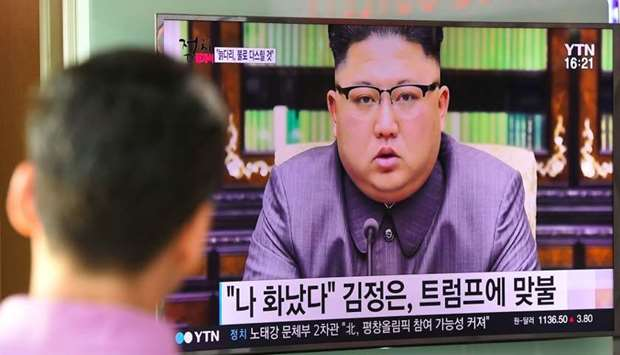 A man watches a television news screen showing a picture of North Korean leader Kim Jong-Un