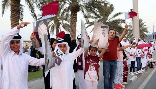 People wait along Doha Corniche for HH the Emir's entourage