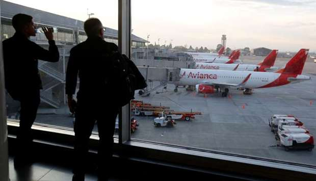 Passengers look at aircraft of Colombian airlines Avianca as the airline's flights are cancelled due