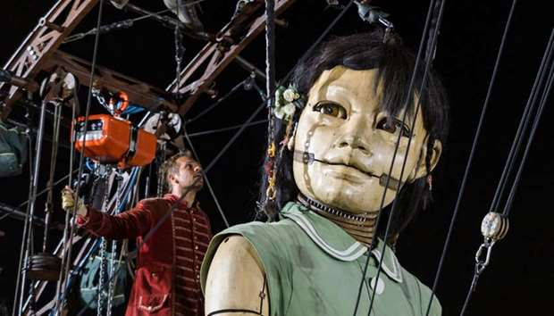 A so-called 'Lilliputian' stands behind an animated marionette called 'The Little Girl Giant'