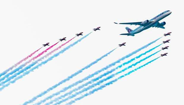 Qatar Airways Airbus A350 and the Red Arrows fly in formation over Doha Corniche