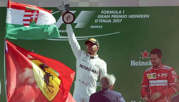 Mercedes' Lewis Hamilton celebrates winning the race with the trophy