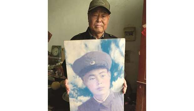 Xiao with a portrait of himself as a young soldier in the Chinese army in the 1950s.