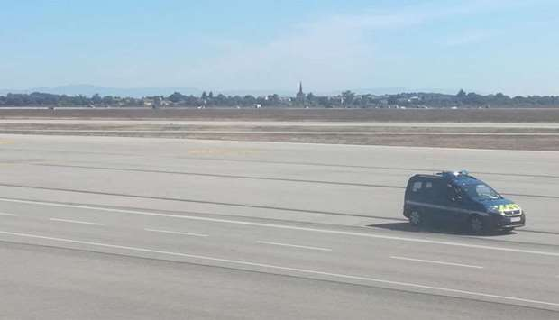 a French gendarmes vehicle speeds on the tarmac of Lyon's Saint-Exupery airport