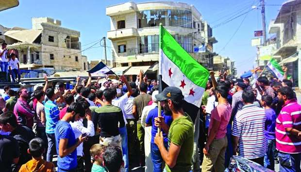 Syrians chant slogans and wave flags of the opposition as they protest against the regime and its al
