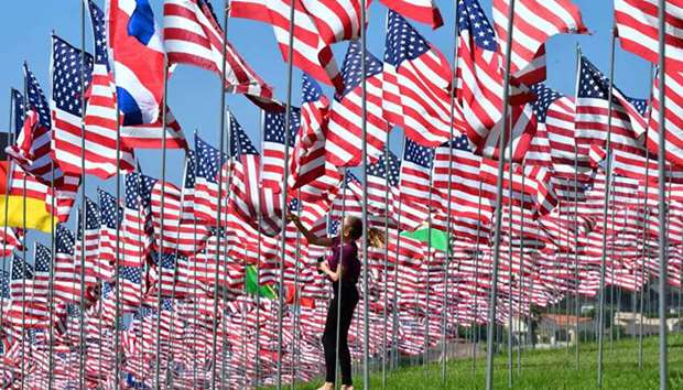 A girl touches a flag as people visit the 'Waves of Flags' display at Pepperdine University in Malib