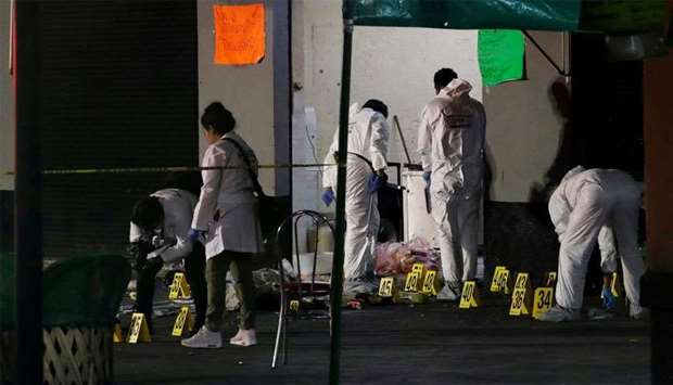 Forensic technicians works at a crime scene where three men were gunned down by unknown assailants a