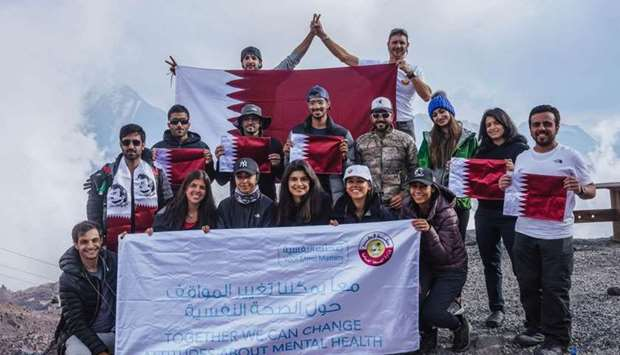 The group at the summit of Mount Elbrus raising Qatari flag with a number of Kuwaiti youth