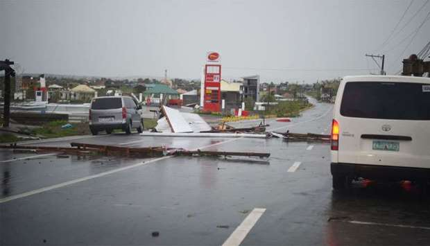 Vehicles maneouver along debris scattered along a road blown by strong winds after Typhoon Mangkhut