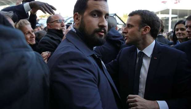 French President Emmanuel Macron (R) shaking hands security officer Alexandre Benalla (C) looks on