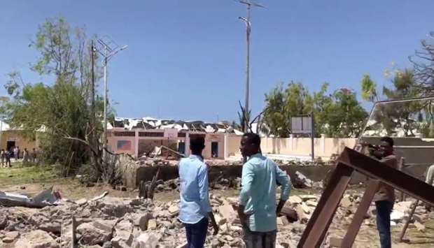 People look at debris at the site of a blast in Mogadishu, Somalia