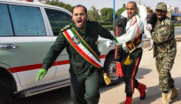 An Iranian soldier carrying an injured comrade at the scene of an attack on military parade