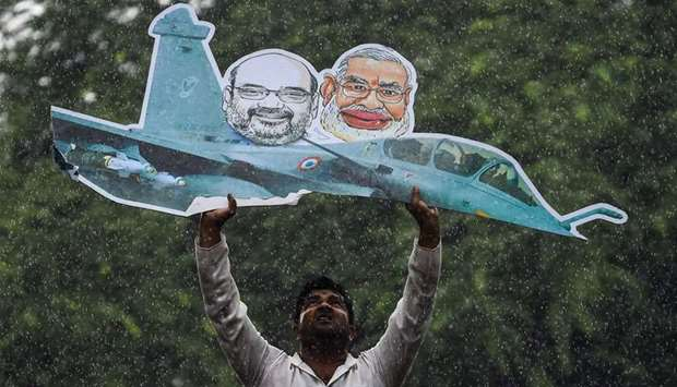 A supporter of the Indian Youth Congress holds a model of a Rafale fighter jet during a protest in N