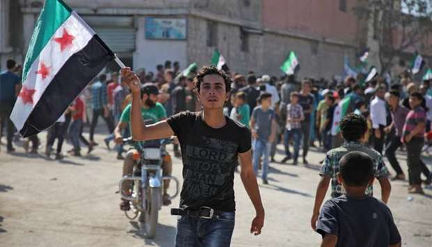 A Syrian youth waves an opposition flag during a demonstration against the Syrian government in the