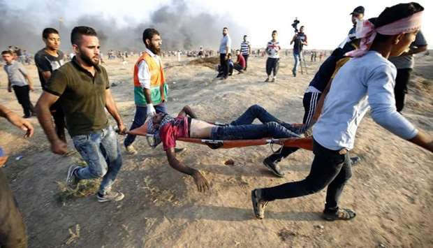 Demonstrators carry an injured Palestinian during clashes along the Israeli border fence, east of Ga