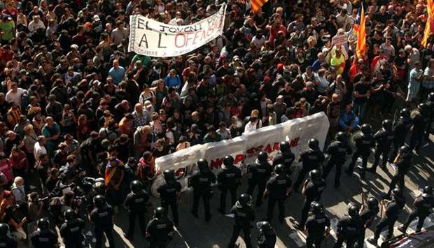 Catalan separatist protesters stand in front of Mossos d'Esquadra police officers before clashing du
