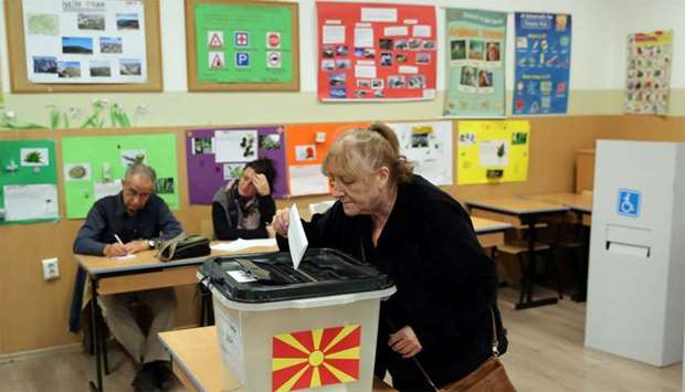 A woman casts her ballot for the referendum in Macedonia on changing the country's name that would o