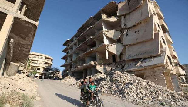 Syrian men ride a motorcycle past heavily-damaged buildings in the rebel-held town of Maaret al-Numa