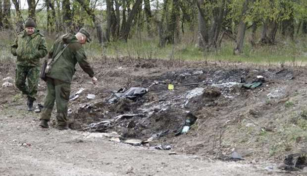 Servicemen inspect a site where a vehicle struck a landmine and exploded, near the village of Pryshy