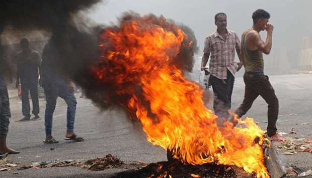 Protesters block a street with burning tires after the Yemeni Riyal has severely plunged against for