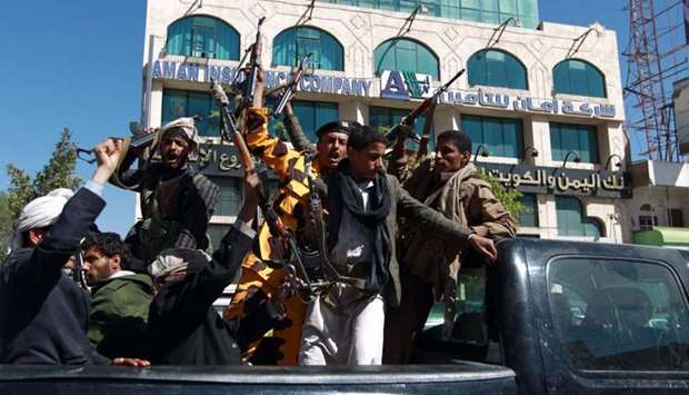 Houthi fighters shout slogans as they ride the back of a pick up in the Yemeni capital Sanaa.