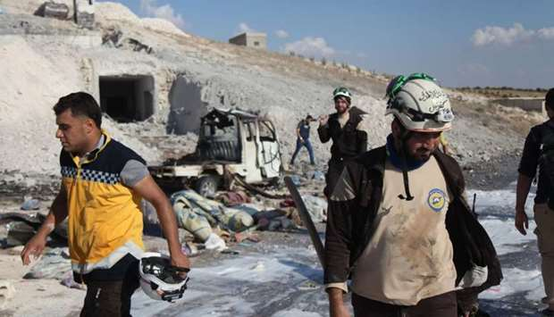 Syrian civil defence members search near a burned vehicle and personal belongings at a site in Hass