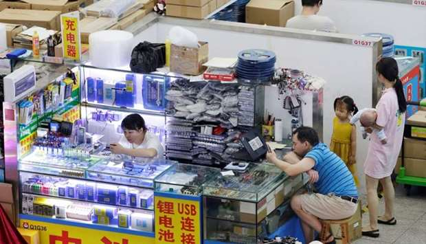 People are seen at stalls inside an electronics mall on Huaqiangbei Commercial Street, a marketplace
