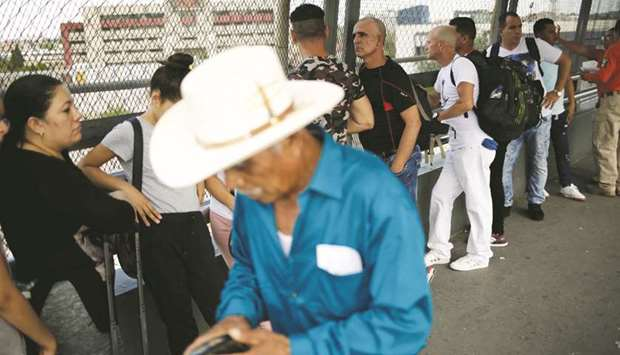 Cuban migrants queue while waiting for US Customs and Border Protection (CBP) agents, to cross into
