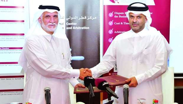 Dr Sheikh Thani and Dr al-Emadi shaking hands after signing the agreement