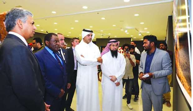 Artists brief Saif Saeed al-Dosari and other attendees about their works.