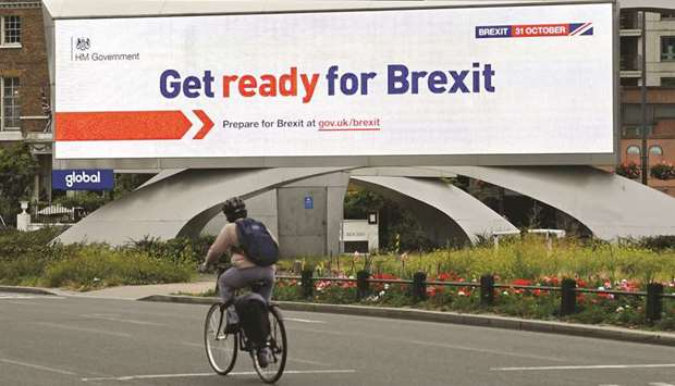 A cyclist rides past an electronic billboard displaying a government Brexit information awareness ca