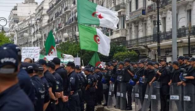Algerian protesters wave their national flags next to security forces during a demonstration against