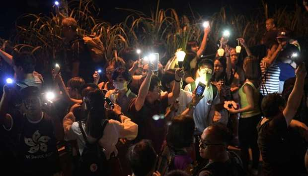 Pro-democracy demonstrators use the torch lights of their phones and hold lanterns while forming a h