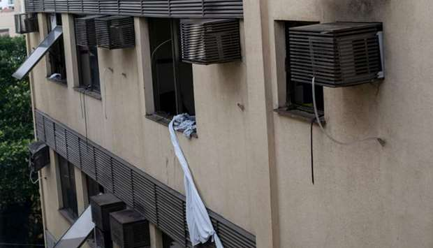 Sheets tied together hang from a window of the Badim private Hospital following a fire at the Tijuca