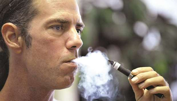 Tyler Bush, manager of The Vapor Bar in Grapevine, Texas, puffs on an electronic cigarette.