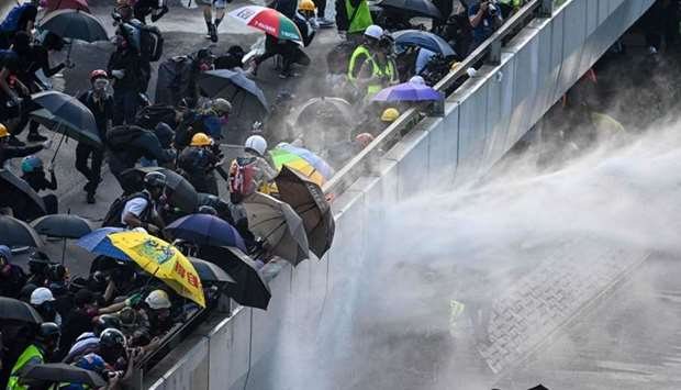 Pro-democracy protesters react as police fire water cannons outside the government headquarters in H